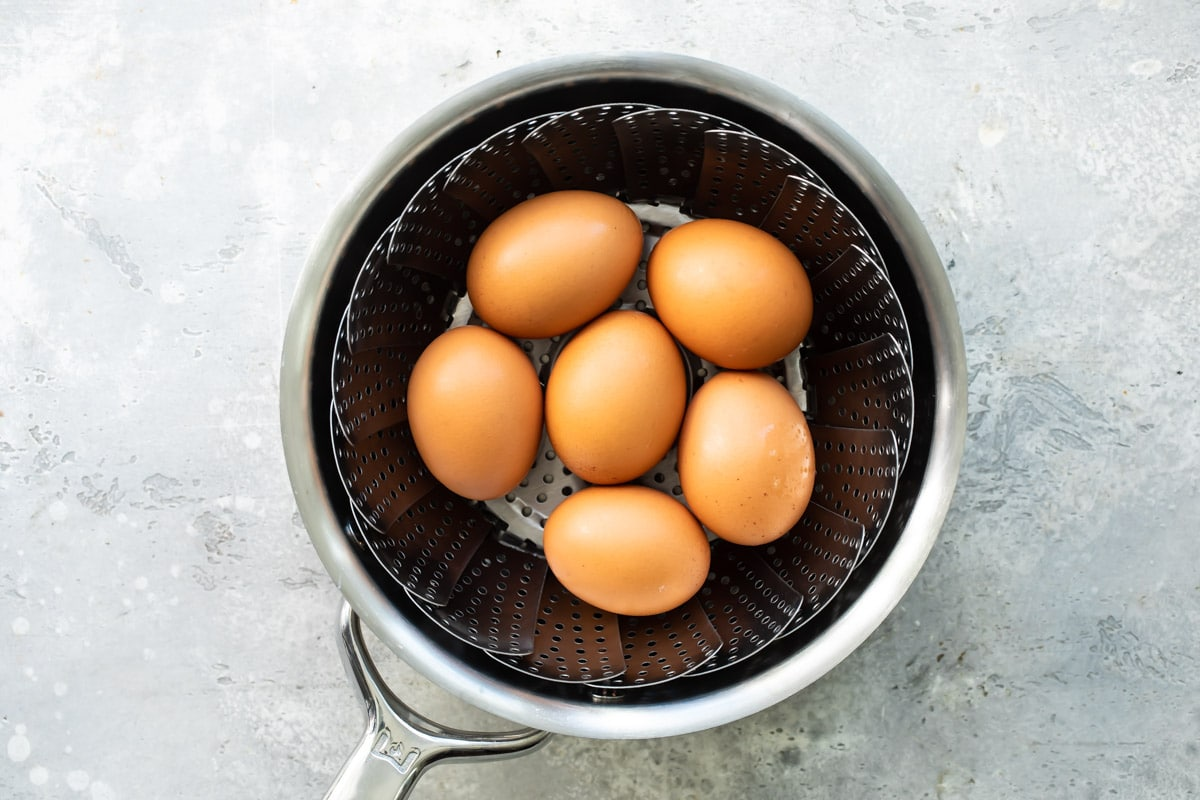 Eggs hard-boiling in a pot of water.