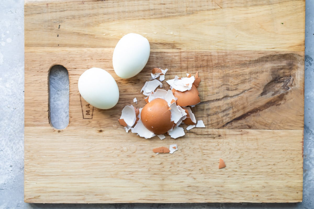 Two hard-boiled eggs peeled on a cutting board.