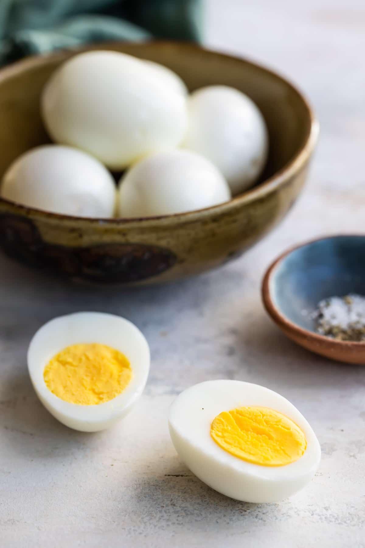 Hard-boiled eggs in a bowl, one split in half in front.