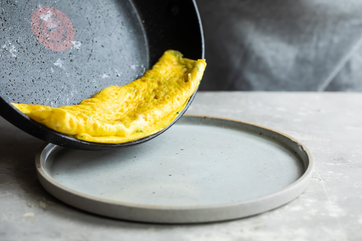 An omelet on a gray plate with a side of fruit.