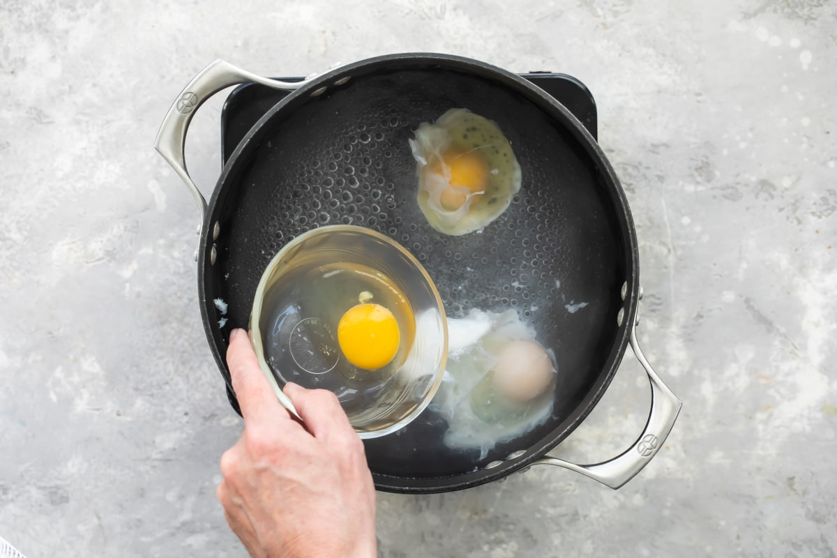 Putting eggs in vinegar water for poaching.