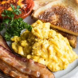 Scrambled eggs on a plate with toast triangles, bacon slices, parsley, and a roasted tomato.
