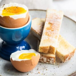 A soft boiled egg in a blue egg cup with toast sticks next to it.