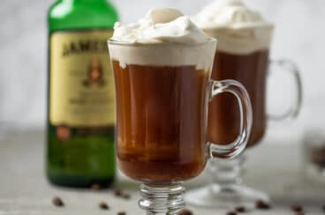 Irish coffee in a glass with whipped cream on top.