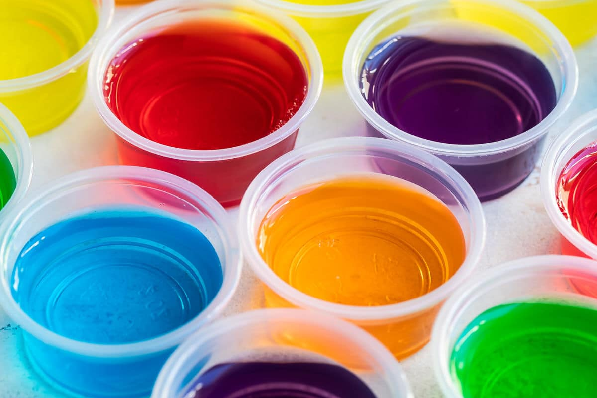 Various colored jello shots in clear portion cups.