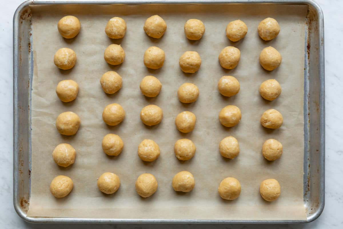 Oreo Cookie balls rolled and set on a baking sheet to freeze.