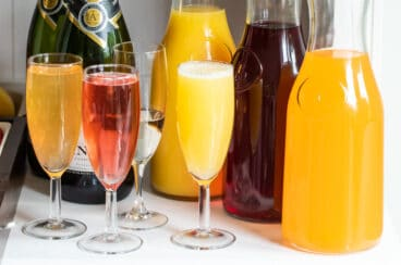 Three carafes with various juices and 4 champagne flutes with mimosas.