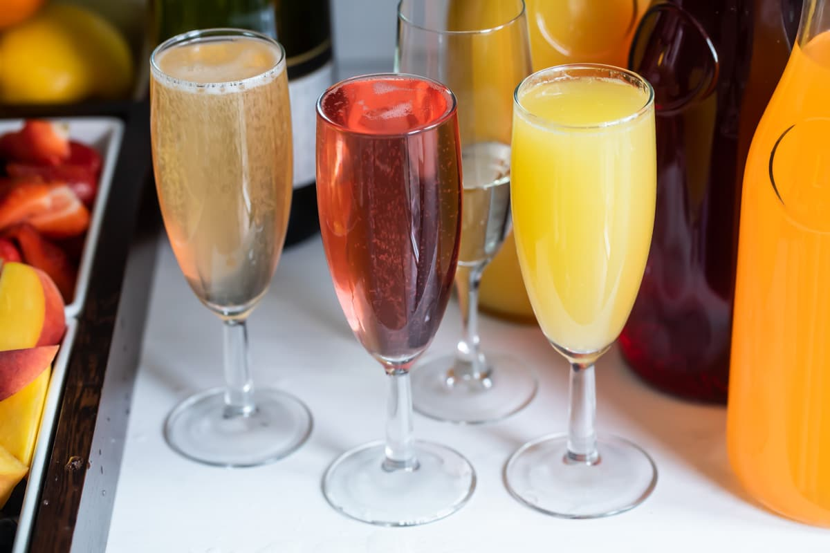 Carafes of juice, bottles of sparkling wine, and fresh fruit garnishes for a mimosa bar.