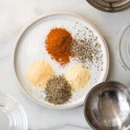 Rotisserie chicken seasoning ingredients on a white plate.