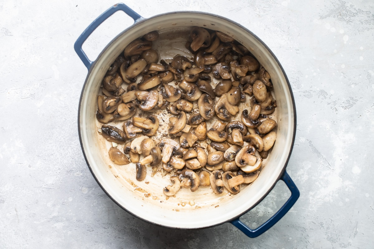 Mushrooms cooking down in a stock pot.