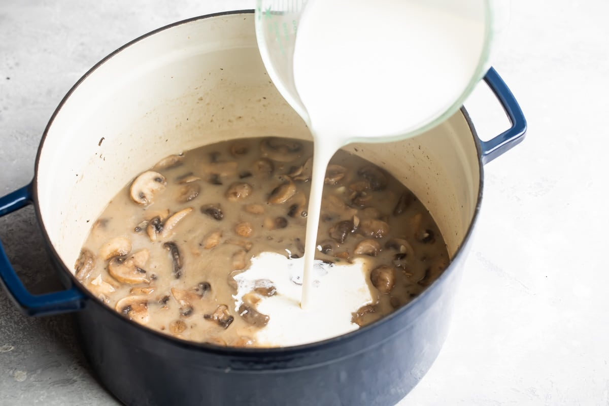 Adding cream to mushroom soup.