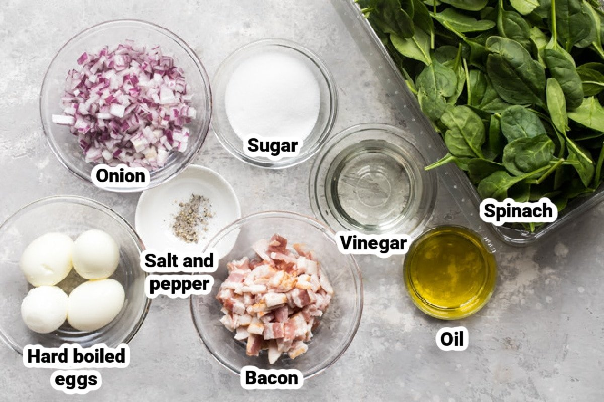 Spinach salad with bacon dressing ingredients in various bowls.