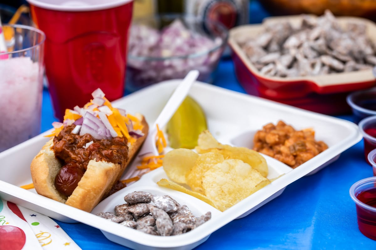 A plate at a tailgate with a chili dog, pickle, puppy chow, chips and baked beans.