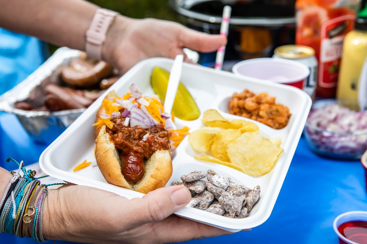 A white divided plate filled with tailgating foods.