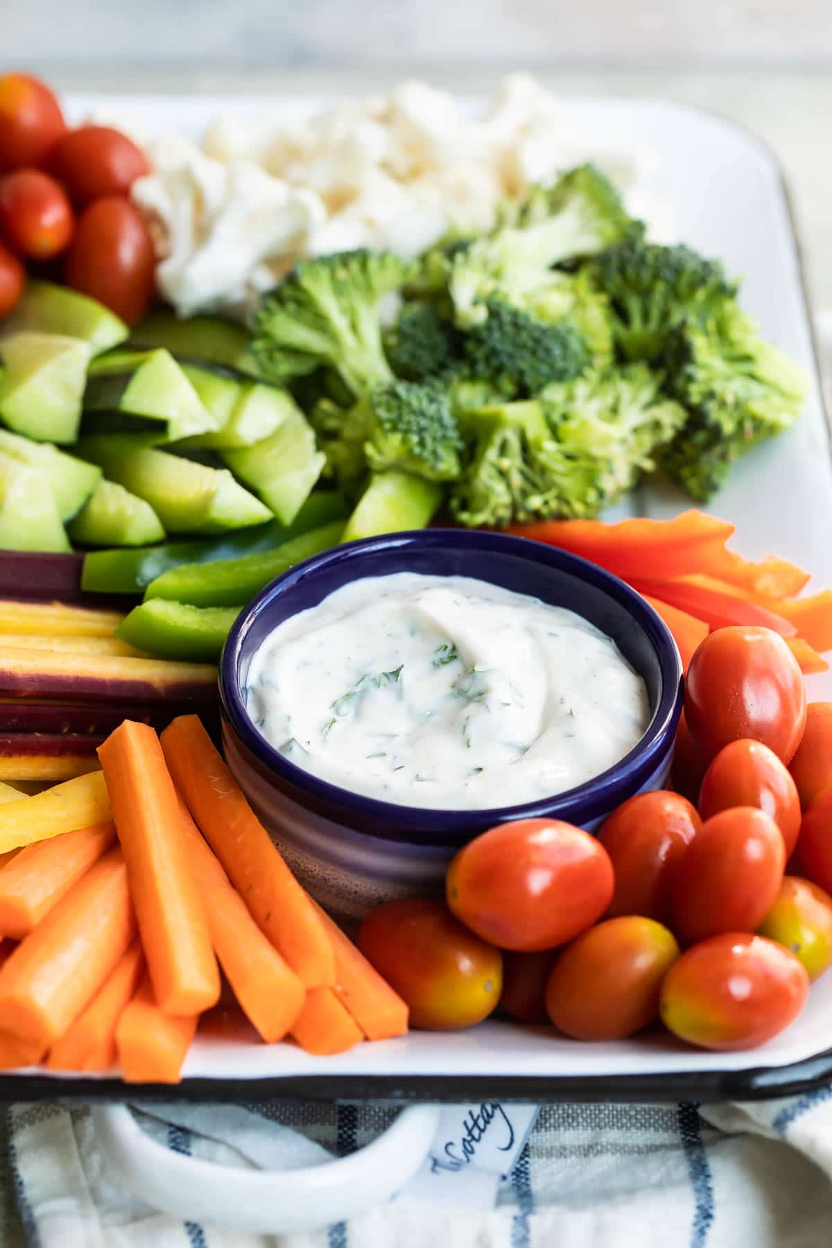 Veggie dip in a navy bowl bowl on a platter surrounded by vegetables.