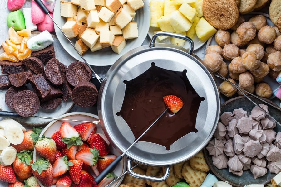 Chocolate fondue served with candy, cookies, cake, and fresh fruit.