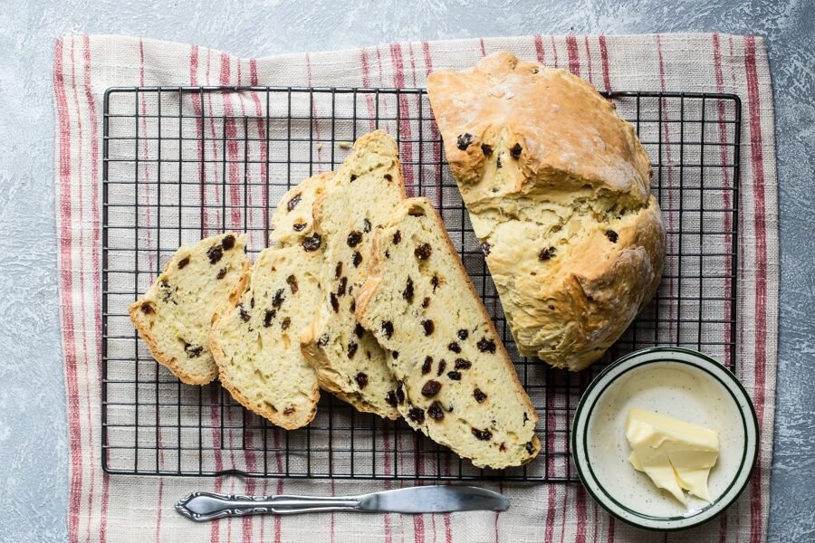 Irish soda bread sliced on a baking rack.