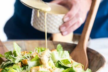 Someone spooning Caesar dressing on a Caesar salad.