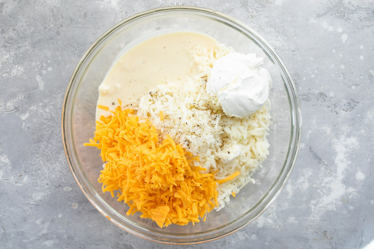 Cheesy potato casserole ingredients in a bowl before mixing.