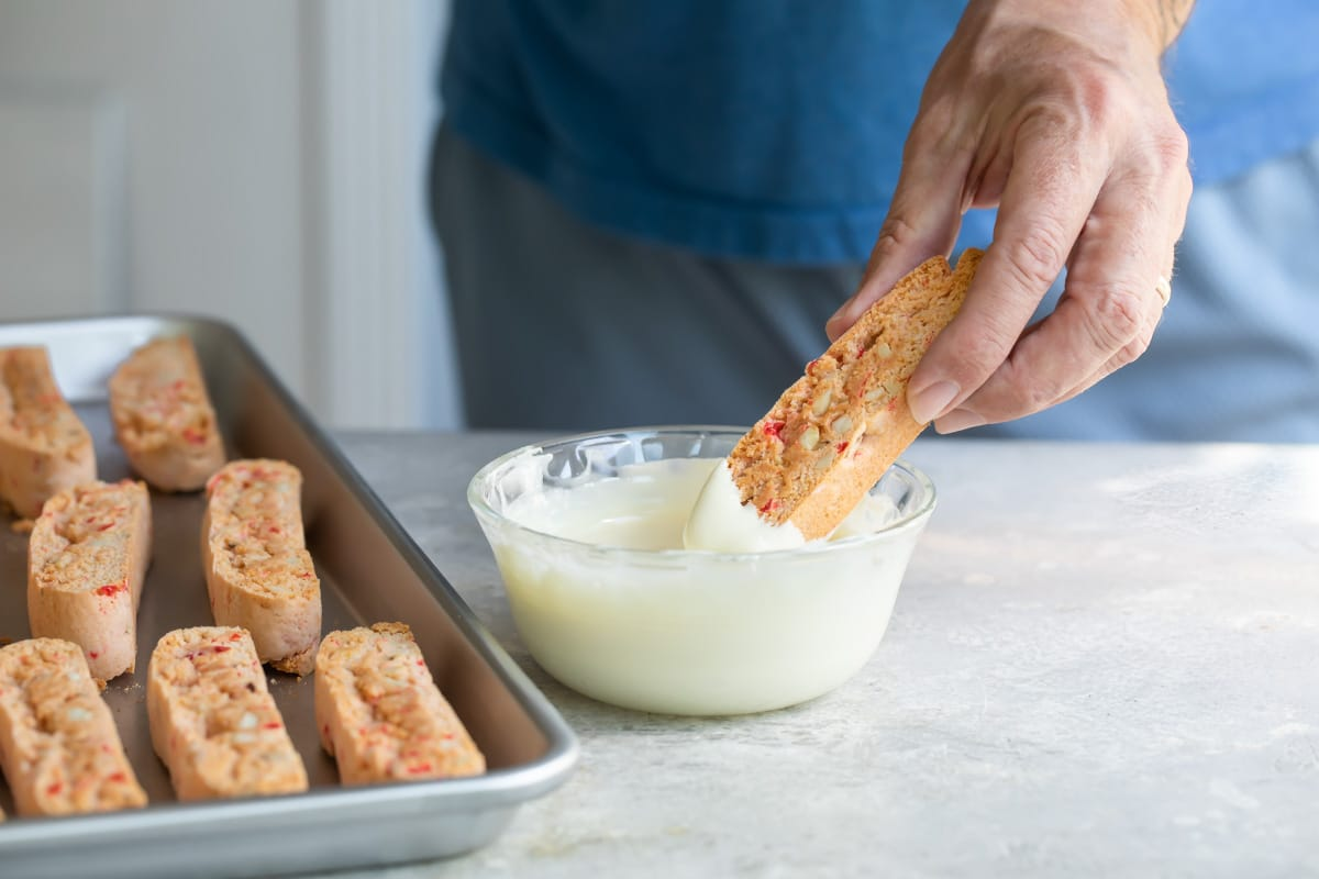 Cherry almond biscotti being dunked in melted white chocolate.