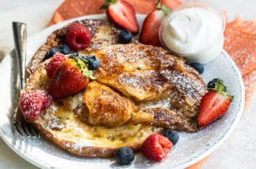 Croissant French toast on a white plate with fruit and whipped cream.