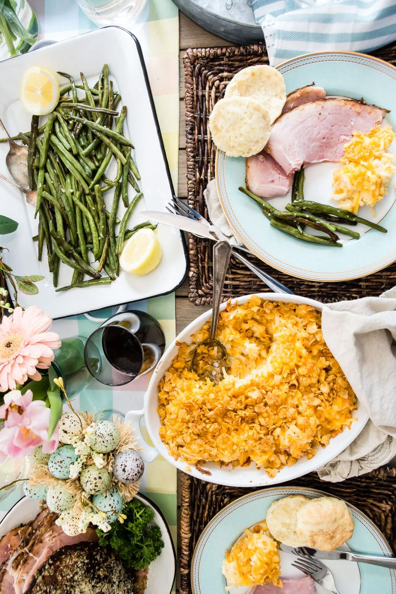 A table set for Easter with baked ham, scalloped potatoes, roasted green beans, and homemade biscuits.