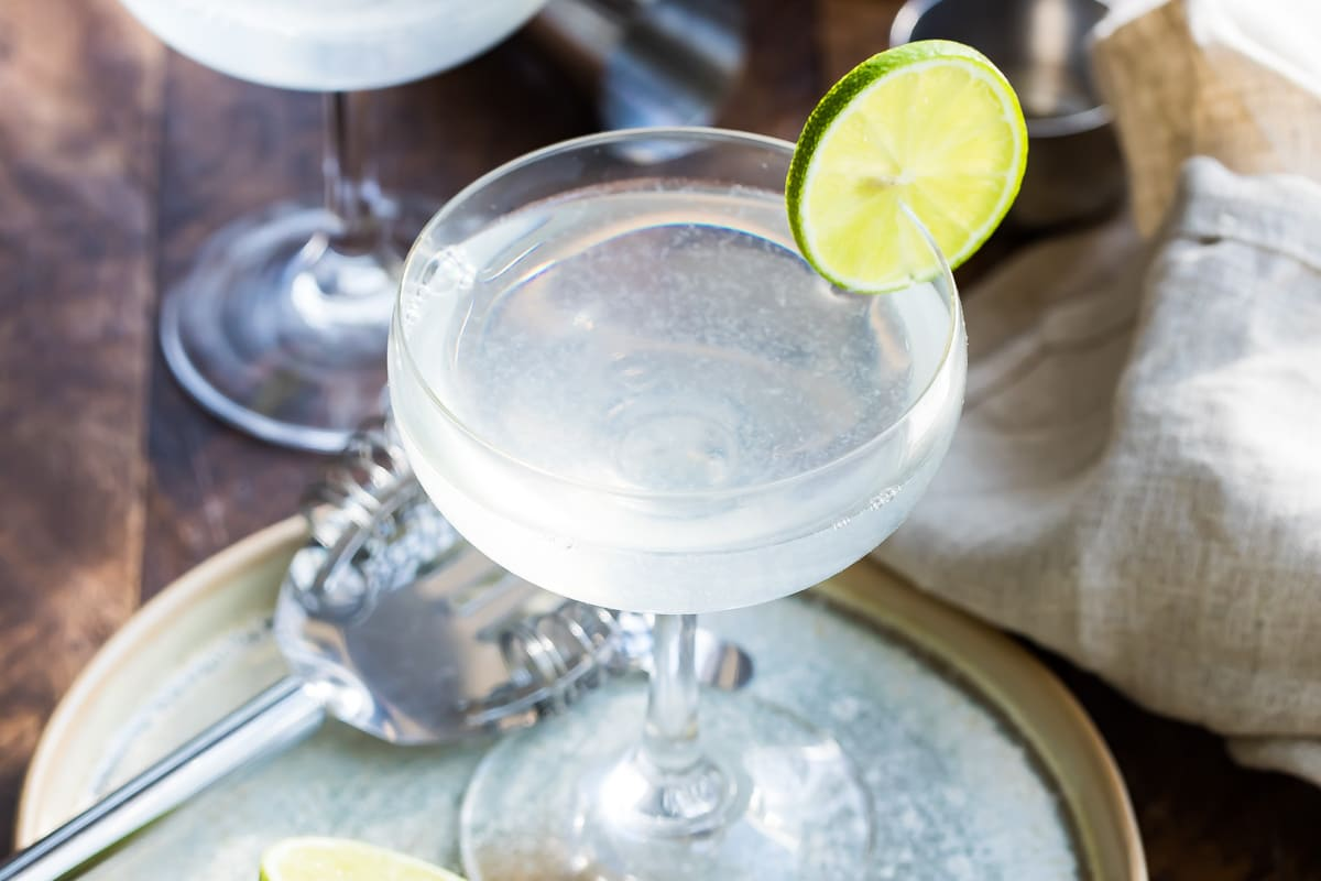 Gimlets in stemmed glasses with lime slices.