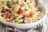 Greek pasta salad in a white bowl.