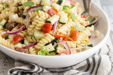 Greek pasta salad in a white bowl.