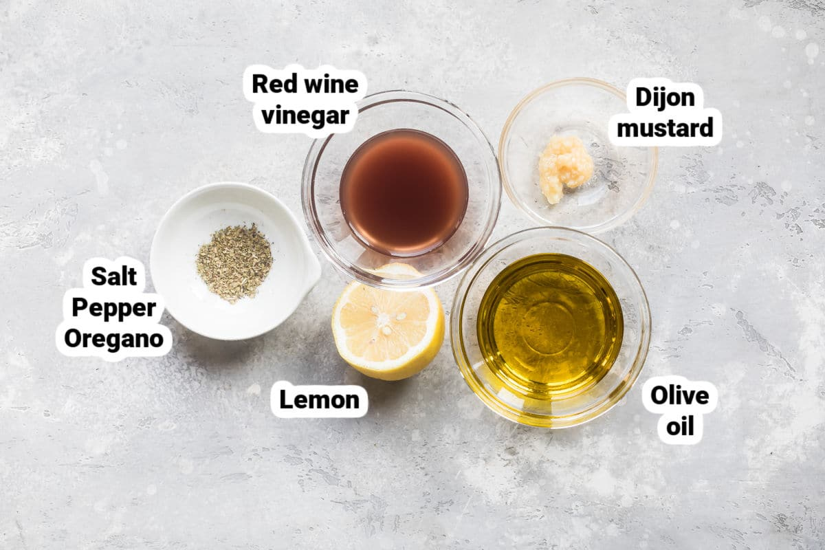 Greek salad dressing ingredients labeled in bowls.