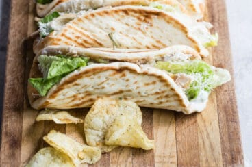 Grilled chicken Caesar wraps on a wood cutting board with chips.