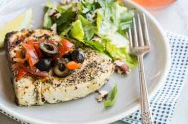 A piece of grilled swordfish on a plate with olive topping and green salad.