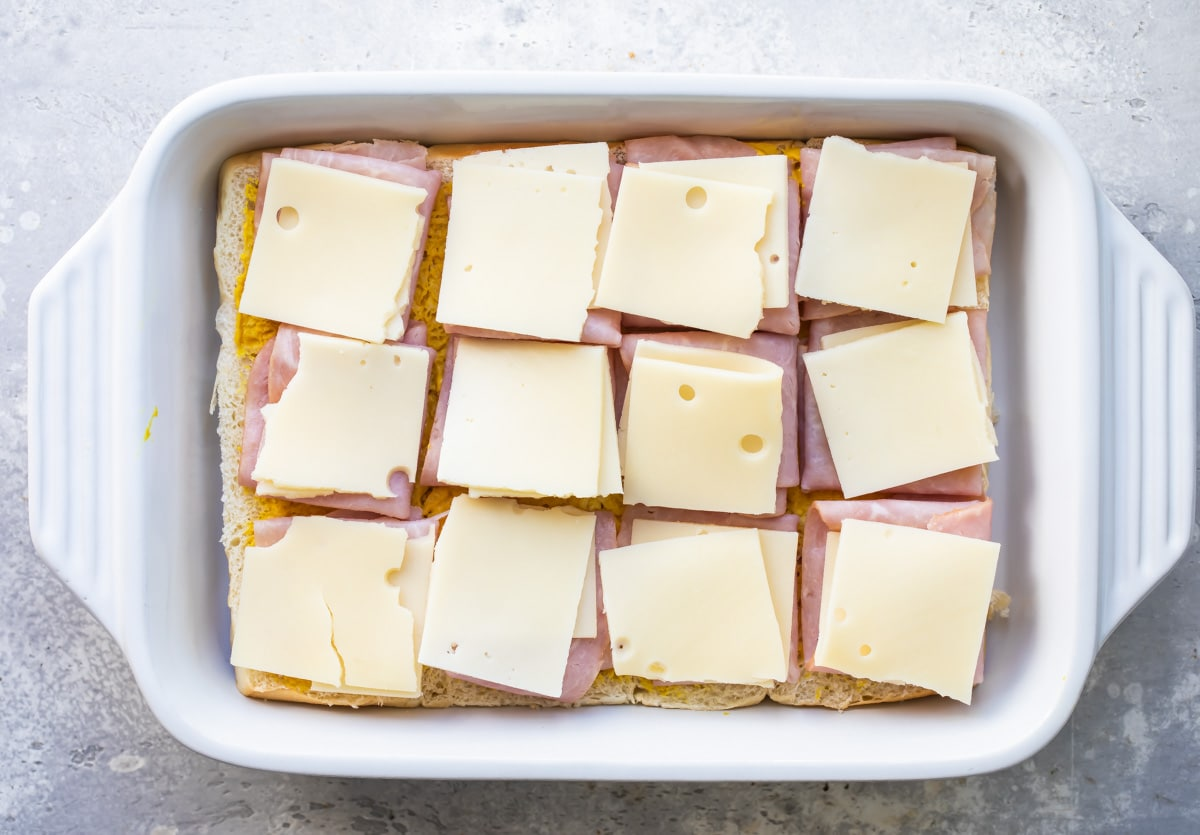 Building ham and cheese sliders in a baking dish.