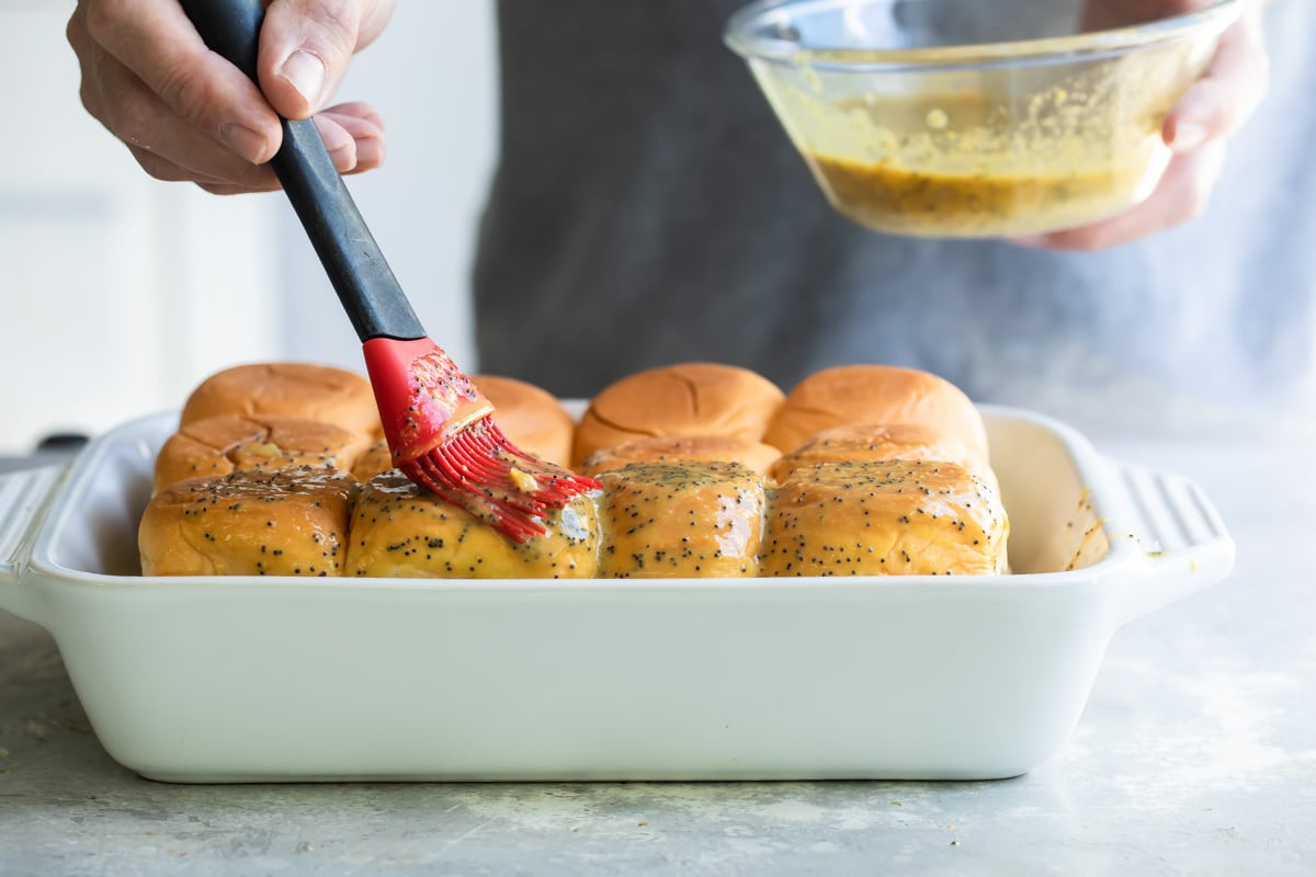 Brushing butter topping on ham and cheese sliders in a baking dish.