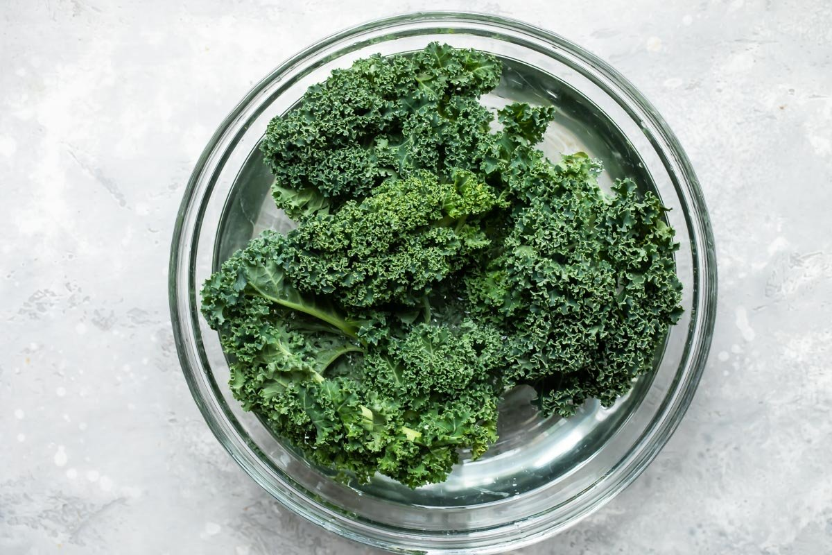 Cleaning kale in a bowl of water.