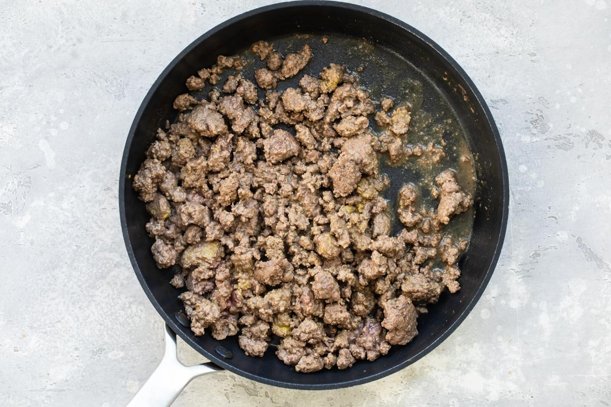 Ground beef cooking in a skillet.