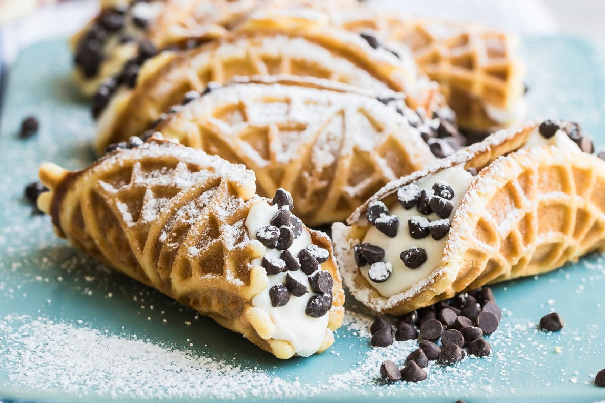 Mock italian cannoli with pizzelle on top of a blue cutting board covered in powdered sugar.