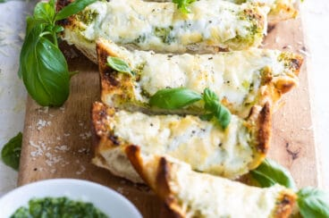 Slices of pesto cheese bread surrounded by basil leaves on a wooden cutting board.