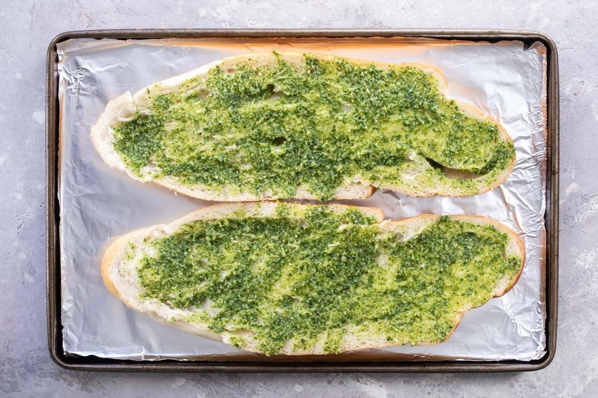 Pesto spread on halves of French bread.