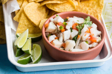 Taliapa ceviche in a pink bowl on a white platter with tortilla chips.