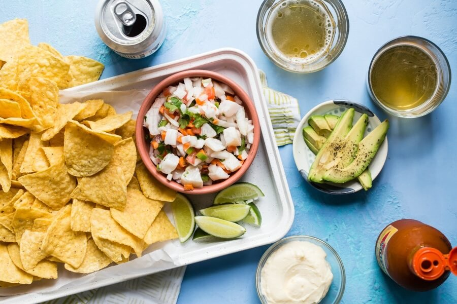 An overhead shot of taliapa ceviche in a pink bowl on a white platter with tortilla chips.