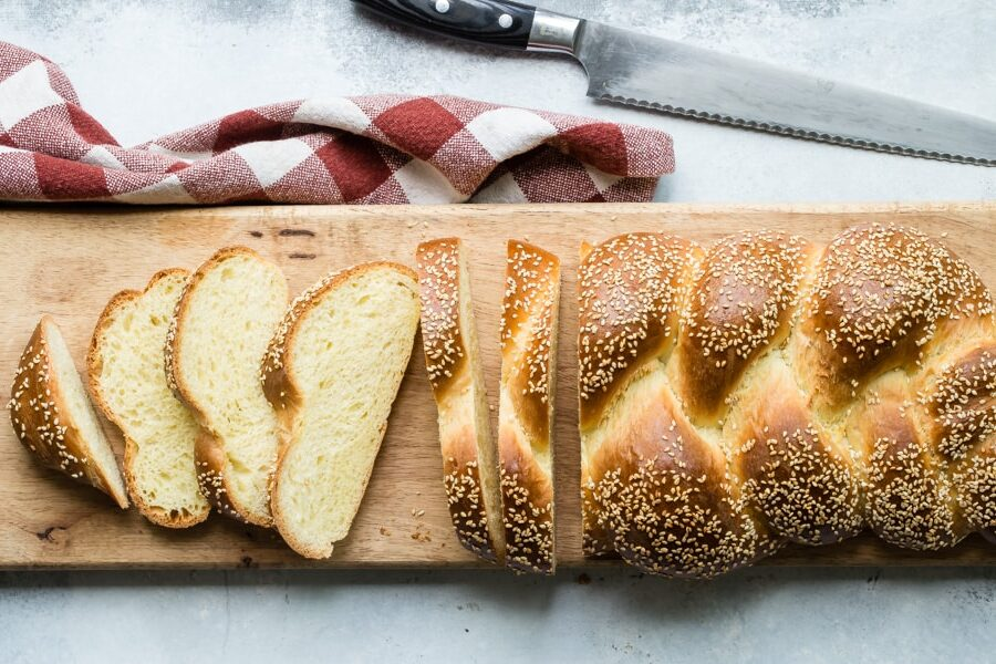 An overhead shot of slices of challah on a wood cutting board.