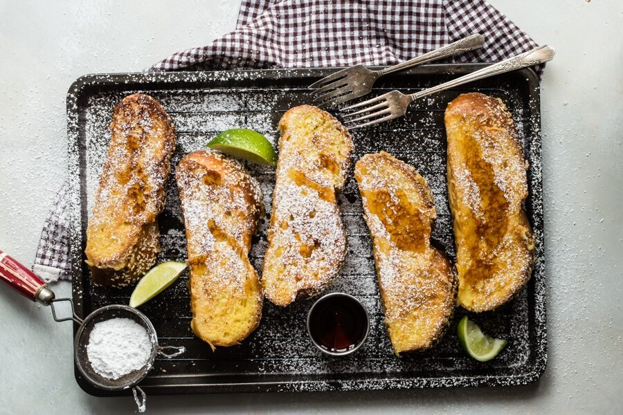 An overhead shot of challah french toast covered with powdered sugar and syrup on a black cookie sheet.