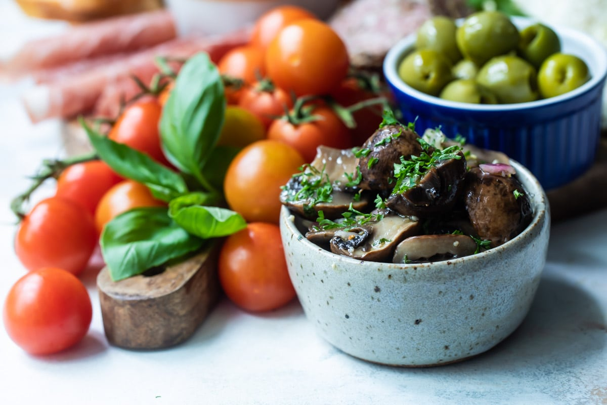 Marinated mushrooms in a gray bowl with vegetables behind them.
