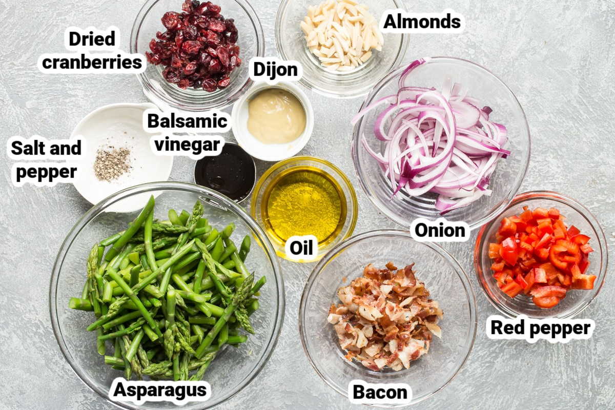 Labeled ingredients for asparagus salad in various bowls.