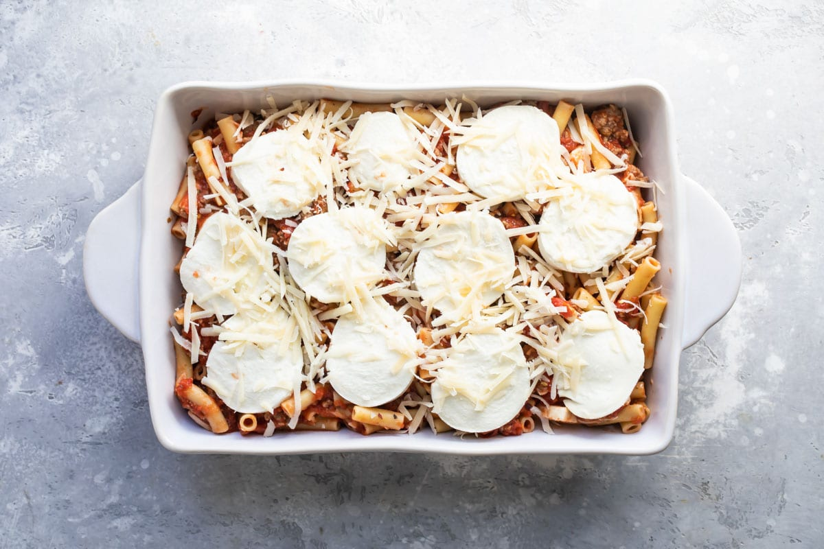 Baked ziti in a white baking dish before being baked.