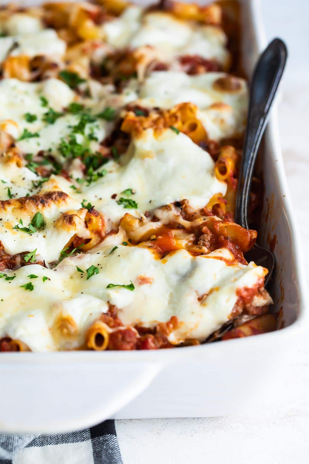 A pan of baked ziti with a spoon in it.