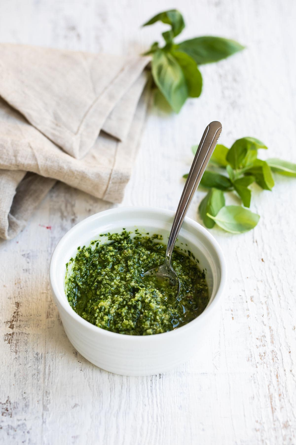 A bowl of pesto with a spoon in it.