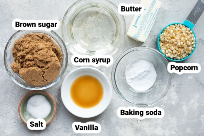 Labeled ingredients for caramel corn in various bowls.