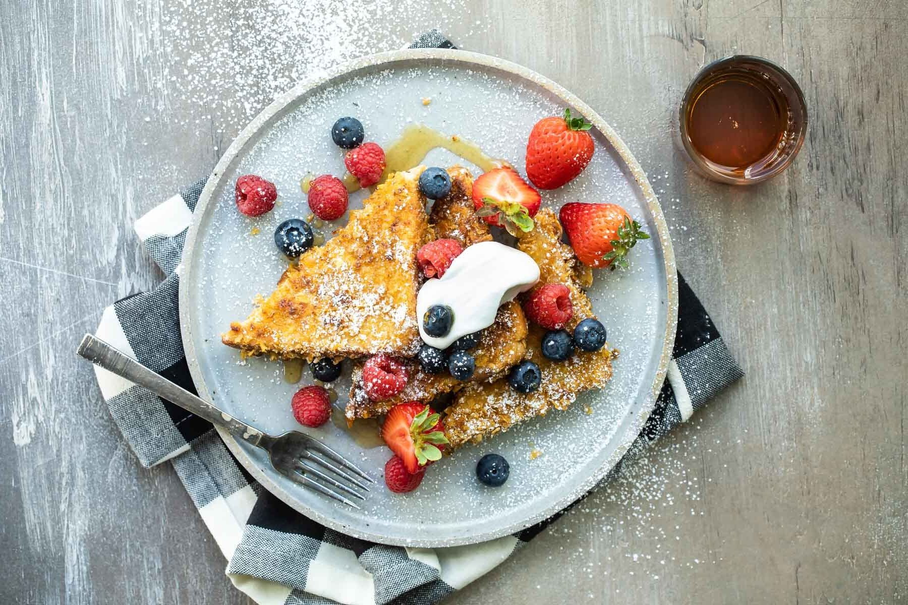 A plate of cornflake crusted french toast with fruit.